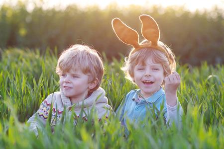 pascuas navide�as: Dos ni�os jugando con orejas de conejo de Pascua jugando en la hierba verde en las vacaciones de Pascua