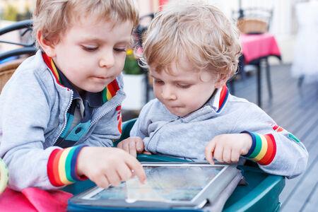 ni�os estudiando: Dos ni�os peque�os hermanos que se divierten junto con tablet pc Foto de archivo