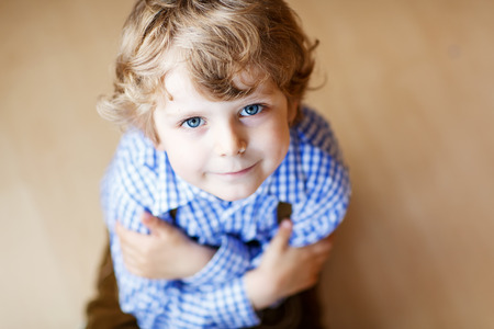 Portrait of adorable little boy with blond hairs and blue eyes, indoor.