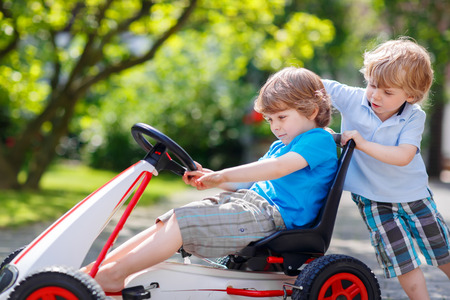 Two funny twins boys having fun with toy race car in summer garden, outdoors. Adorable brother pushing the car with another child. Outdoor games for children in summer concept. Stock Photo