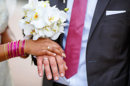 Beautiful indian bride and caucasian groom, after wedding ceremony. hands of man and woman with rings and traditional indian jewelry photo