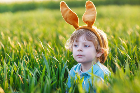 animal ear: Cute little child with Easter bunny ears playing in green grass on sunny spring day, celebrating Easter holiday