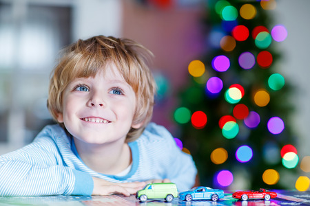 Little blond child playing with cars and toys at home, indoor. Cute happy funny boy having fun with gifts. Colorful lights on background Standard-Bild