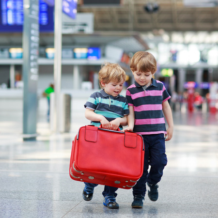 Two little sibling boys having fun and going on vacations trip with suitcase at intrernational airport, indoors. Kids and friends holding red suitcase and walking to the gate.