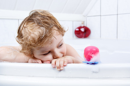 little girl bath: Happy cute little  blond toddler boy having fun with water by taking bath in bathtub at home. Funny kid splashing and playing with toys.