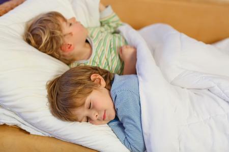 Dva malí blond sourozenecké kluci spí v posteli. Unavení děti snění a relaxaci. Šťastná rodina dvou bratrů.