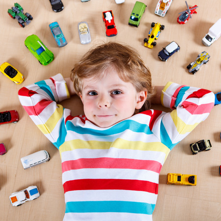 3 4 years: Little blond child playing with lots of toy cars indoor. Kid boy wearing colorful shirt and having fun.