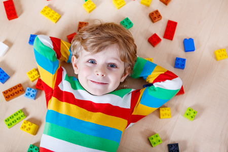 kids activities: Little blond child playing with lots of colorful plastic blocks indoor. Kid boy wearing colorful shirt and having fun with building and creating.