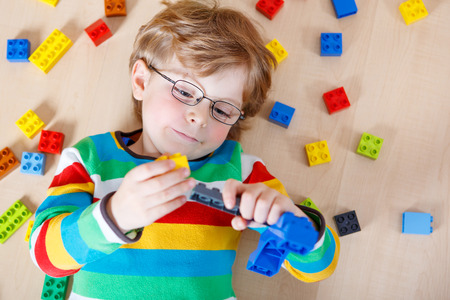 kids activities: Little blond kid boy playing with lots of colorful plastic blocks indoor. child wearing colorful shirt and glasses, having fun with building and creating.