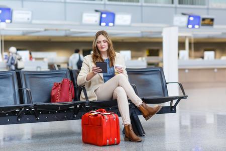 femme valise: Jeune femme � l'a�roport international, la lecture de son ordinateur ebook et de boire du caf� pour aller en attendant son vol. Femme passagers au terminal, � l'int�rieur.