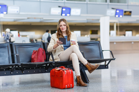 Young woman at international airport, reading her ebook computer and drinking coffee to go while waiting for her flight. Female passenger at terminal, indoors. Stock Photo
