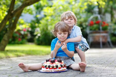 Funny cute kid celebrating his third birthday in homes garden with big cake. His brother hugging him. Two little children having fun together. photo