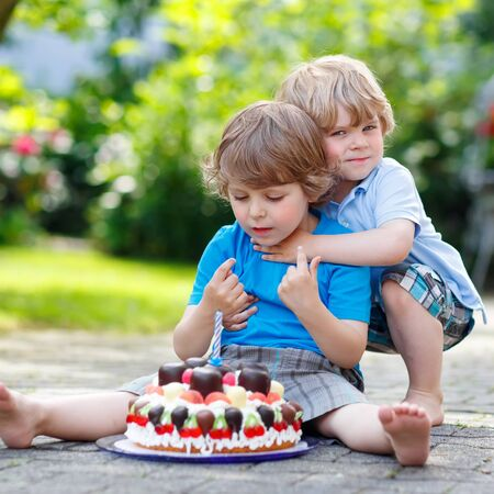 Two little kid boys celebrating birthday in homes garden with big cake.  Two little children having fun with hugging and tasting cake together. photo