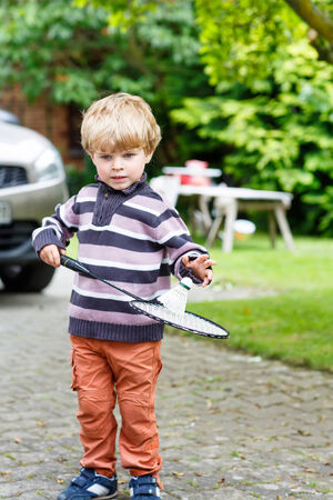 domestic garden: Little cute funny kid boy playing badminton in domestic garden. Active outdoors games and leisure for children lifestyle.