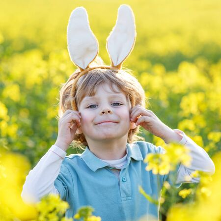 pascuas navide�as: Chico rubio divertido de 3 a�os con orejas de conejo de Pascua jugando violaci�n campo amarillo en d�a soleado de primavera, la celebraci�n de fiesta de Pascua Foto de archivo