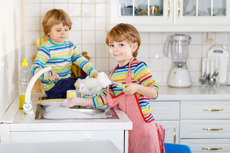 twin house: Two funny little boy friends washing dishes in domestic kitchen. Children having fun with helping with housework. Indoors, kids in colorful clothes. Selective focus