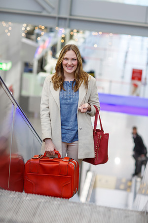 arrive: Young woman at international airport, on escalator at arrival terminal . Female passenger looking forward to arrive home, indoors. Stock Photo