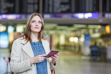 Young woman  at international airport, checking electronic board and waiting for her flight. Female passenger with european passport at departure terminal, indoors.