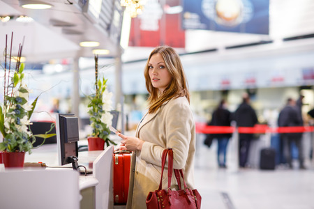 Young woman  at international airport, on check in counter and waiting for her flight. Female passenger with red suitcase and passport at departure terminal, indoors.