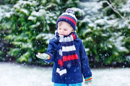 outoors: Cute little funny boy in colorful winter clothes catching snow and snowflakes, outdoors during snowfall. Active outoors leisure with children in winter. Kid with warm hat, hand gloves and scarf