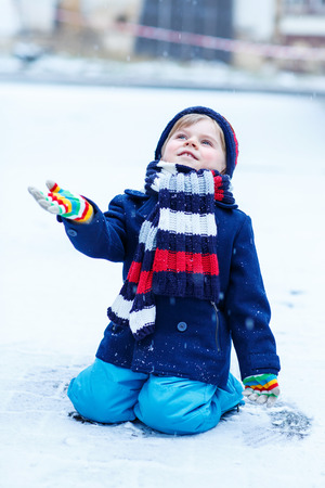 having fun in the snow: Lovely little funny kid in colorful winter clothes having fun with snow, outdoors during snowfall. Active outoors leisure with children in winter. Kid with warm hat, hand gloves and scarf