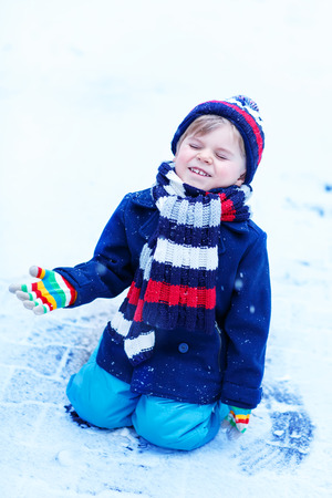having fun in the snow: Funny and happy toddler boy in colorful winter clothes having fun with snow, outdoors during snowfall. Active outoors leisure with children in winter. Kid with warm hat, hand gloves and scarf Stock Photo