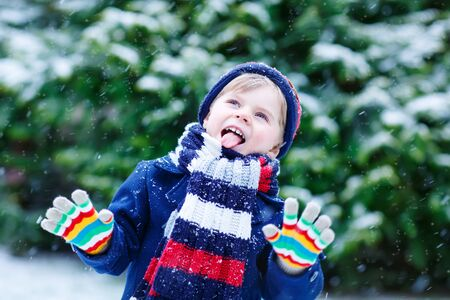 funny people: Cute little funny child in colorful winter clothes having fun with snow, outdoors during snowfall. Active outoors leisure with children in winter. Kid with warm hat, hand gloves and scarf