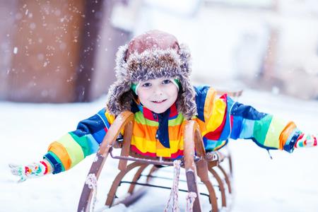 Schattige kleine grappige jongen in kleurrijke winter kleren plezier op sneeuw slee, buitenshuis tijdens sneeuwval. Actieve outoors vrijetijdsbesteding met kinderen in de winter. Kid met warme muts, handschoenen en sjaal met strepen. Geluk over sneeuw.