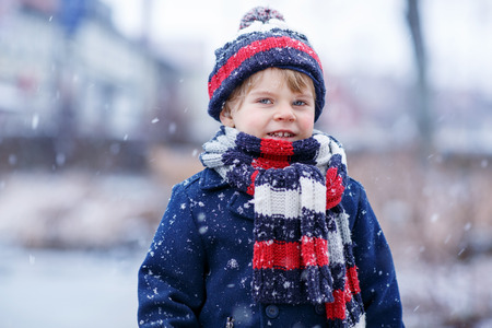 outoors: Winter portrait of kid boy in colorful winter clothes, outdoors during snowfall. Active outoors leisure with children in winter. Kid with warm hat, hand gloves and scarf