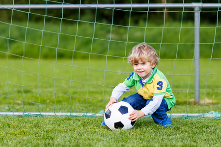 leisure: Funny happy little kid boy playing soccer and football and having fun, outdoors on field. Active leisure with children on warm sunny summer day.