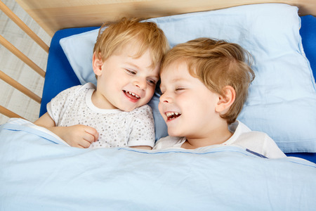 Family Of Two Little Boys Twins Having Fun In Bed At Home Indoors
