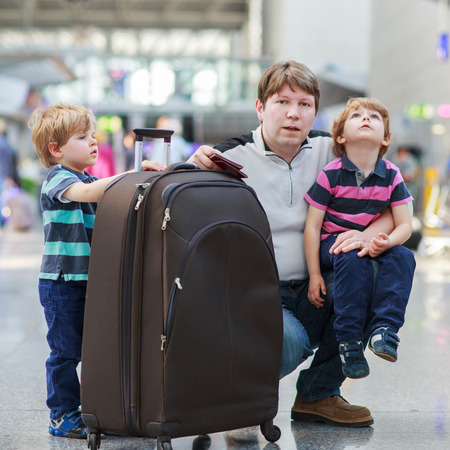 sibling: Happy family of three: Father and two little sibling boys at the airport, traveling together.