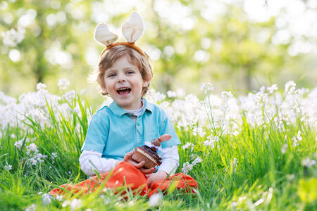 Cute happy little boy wearing Easter bunny ears at spring green grass and blooming apple garden, eating chocolate muffing with bunny and having fun outdoors. photo