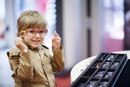 眼鏡でかわいい子供男の子は彼の新しい眼鏡を選択する時に保存します。