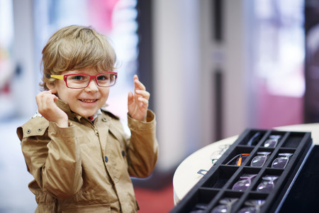 specs: Cute little kid boy at optician store during choosing his new glasses.