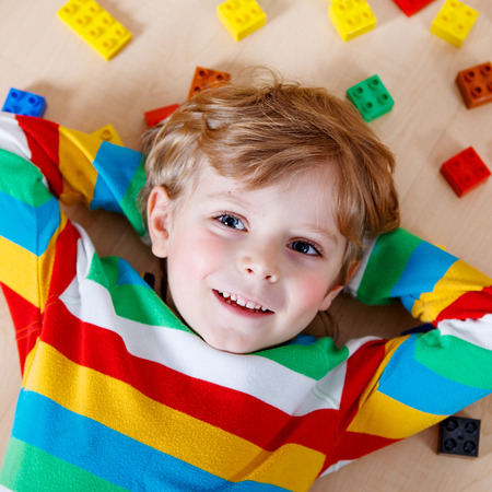 children learning: Little blond child playing with lots of colorful plastic blocks indoor. Kid boy wearing colorful shirt and having fun with building and creating.