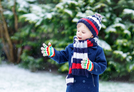 outoors: Active little kid boy in colorful winter clothes having fun with snow, catching snowflakes, outdoors during snowfall on cold day. Active outoors leisure with children in winter.