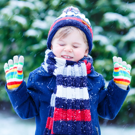 having fun in the snow: Happy little funny child in colorful winter clothes having fun with snow, outdoors during snowfall on cold day. Active outoors leisure with children in winter.