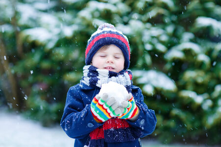 having fun in the snow: Cute little funny child in colorful winter clothes having fun with snow and making ball, outdoors during snowfall on cold day. Active outoors leisure with children in winter. Stock Photo