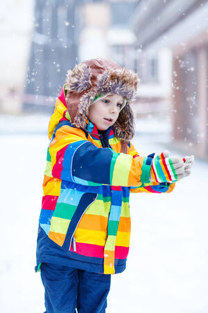 having fun in the snow: Active little preschool boy in colorful winter clothes having fun with snow, catching snowflakes, outdoors during snowfall on cold day. Active outoors leisure with children in winter.