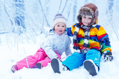 portrait of two kids: boy and girl in winter hat in snow forest at snowflakes background. outdoors winter leisure and lifestyle with children. photo
