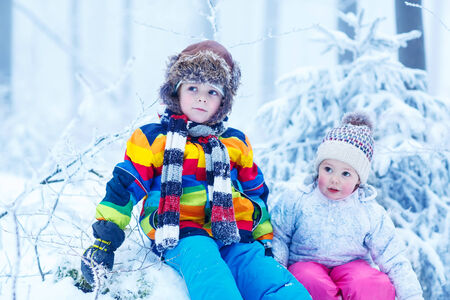 portrait of two kids: boy and girl in winter hat in snow forest at snowflakes background. outdoors winter leisure and lifestyle with children on cold days. photo