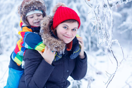 Happy mother and her little son in winter hats in snow forest at snowflakes background. outdoors winter leisure and lifestyle with kids. photo