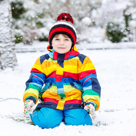 outoors: Funny preschool boy in colorful clothes happy about snow, playing and having fun, outdoors during snowfall on cold day. Active outoors leisure with children in winter.