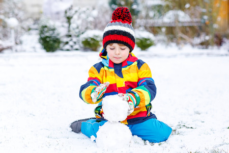 outoors: Funny preschool boy in colorful clothes making a snowman, playing and having fun with snow, outdoors  on cold day. Active outoors leisure with children in winter. Stock Photo