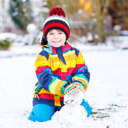 outoors: Beautiful kid boy in colorful clothes making a snowman, playing and having fun with snow, outdoors  on cold day. Active outoors leisure with children in winter.