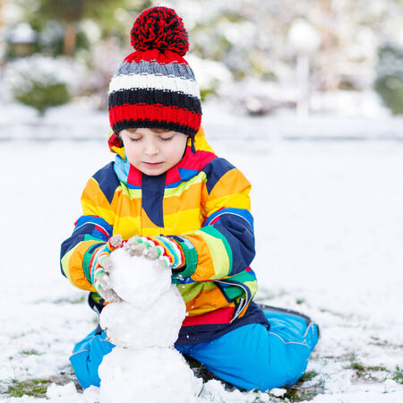 having fun in the snow: Lovely little boy in colorful clothes making a snowman, playing and having fun with snow, outdoors  on cold day. Active outoors leisure with children in winter. Stock Photo