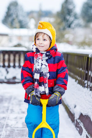 outoors: Funny little boy boy in colorful clothes happy about snow, playing and having fun, outdoors during snowfall on cold day. Active outoors leisure with children in winter. Stock Photo