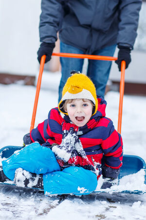 outoors: Funny little child having fun with riding on snow shovel during his father cleaning road from snow, outdoors  on cold day. Active outoors leisure with children in winter.