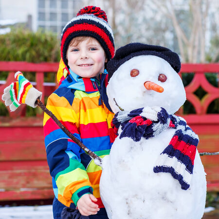 outoors: Funny kid boy in colorful clothes making a snowman, playing and having fun with snow, outdoors  on cold day. Active outoors leisure with children in winter. Stock Photo